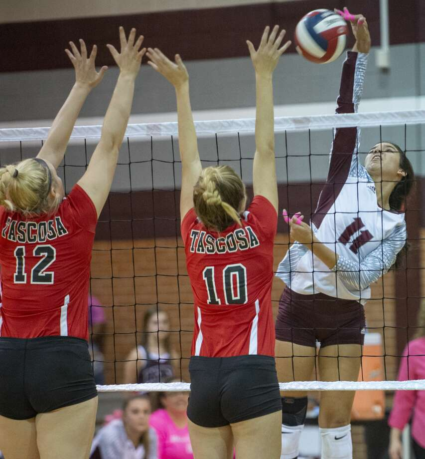 Lee High's Yali Flores goes up for a spike as Tascosa's Taryn Galt and BB Irwin try to block 10/08/19 at Lee High gym. Tim Fischer/Reporter-Telegram Photo: Tim Fischer/Midland Reporter-Telegram
