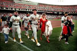 ** FOR USE AS DESIRED WITH EARTHQUAKE ANNIVERSARY STORIES ** In this photo taken On October 17, 1989, Oakland A's Jose Canseco walks off the field with his wife Ester  and other A's players before the start of the World Series at Candlestick Park in San Francisco. Oct. 17, 2009 marks the 20th anniversary of the Loma Prieta earthquake. (AP Photo/Contra Costa Times, Dan Rosenstrauch) ** MAGS OUT; NO SALES; MANDATORY CREDIT **