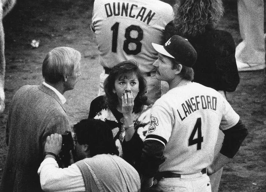Players gather on the field with their families as the Loma Prieta earthquake postpones Game 3 of the 1989 World Series between the Giants and A's. Oakland third baseman Carney Lansford looks toward the stands. Photo: John O'Hara/The Chronicle