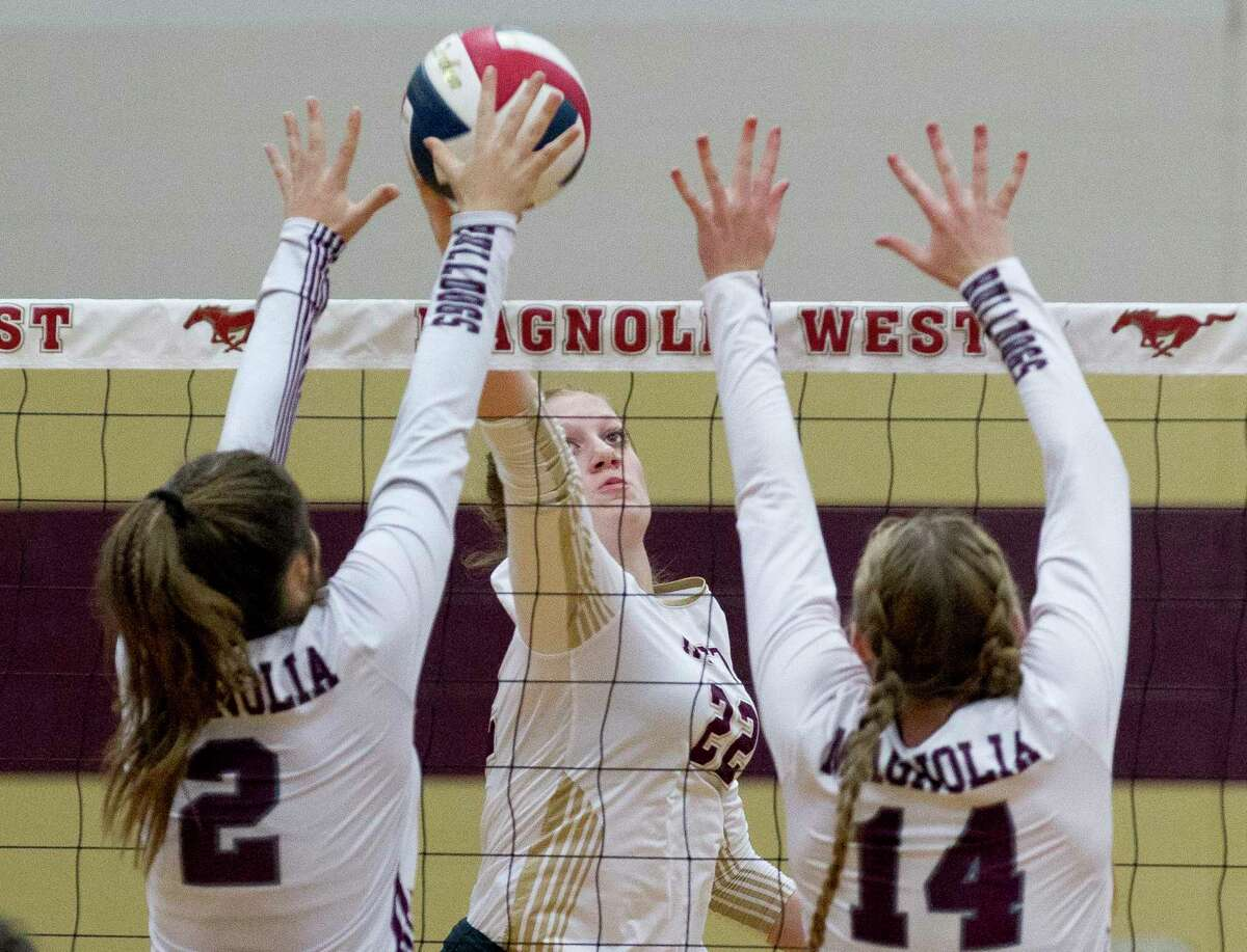 Evyn Snook (22) of Magnolia West has her shot blocked by Magnolia blockers Kendall Boggan (2) and Ellie Anderson (14) during the first set of a District 19-5A high school volleyball match at Magnolia West High School, Tuesday, Oct. 8, 2019, in Magnolia