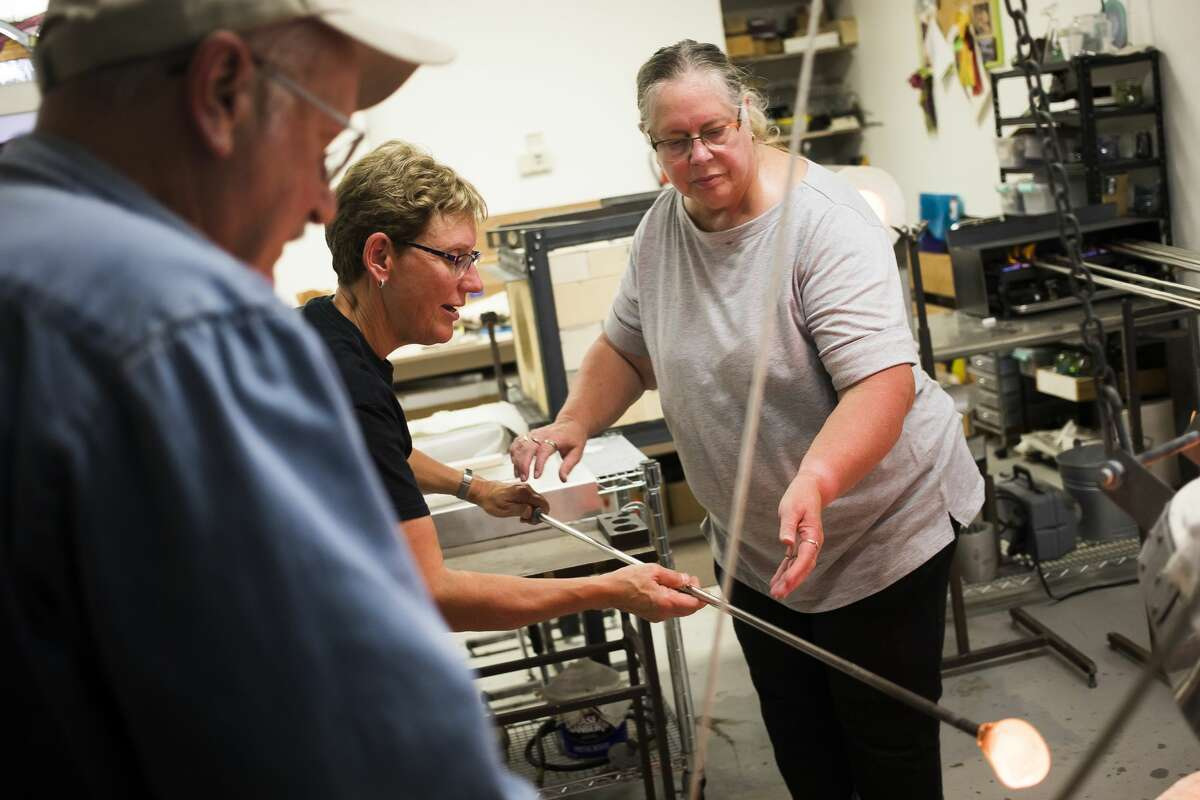 Glass blowing instructor Debra VanTol, left, assists Wendy Gilbert of Frankenmuth, right, in gathering molten glass on a punty rod during the second session of a four-week glass blowing class Wednesday, Oct. 2, 2019 at Village Glass Works in Auburn. (Katy Kildee/kkildee@mdn.net)