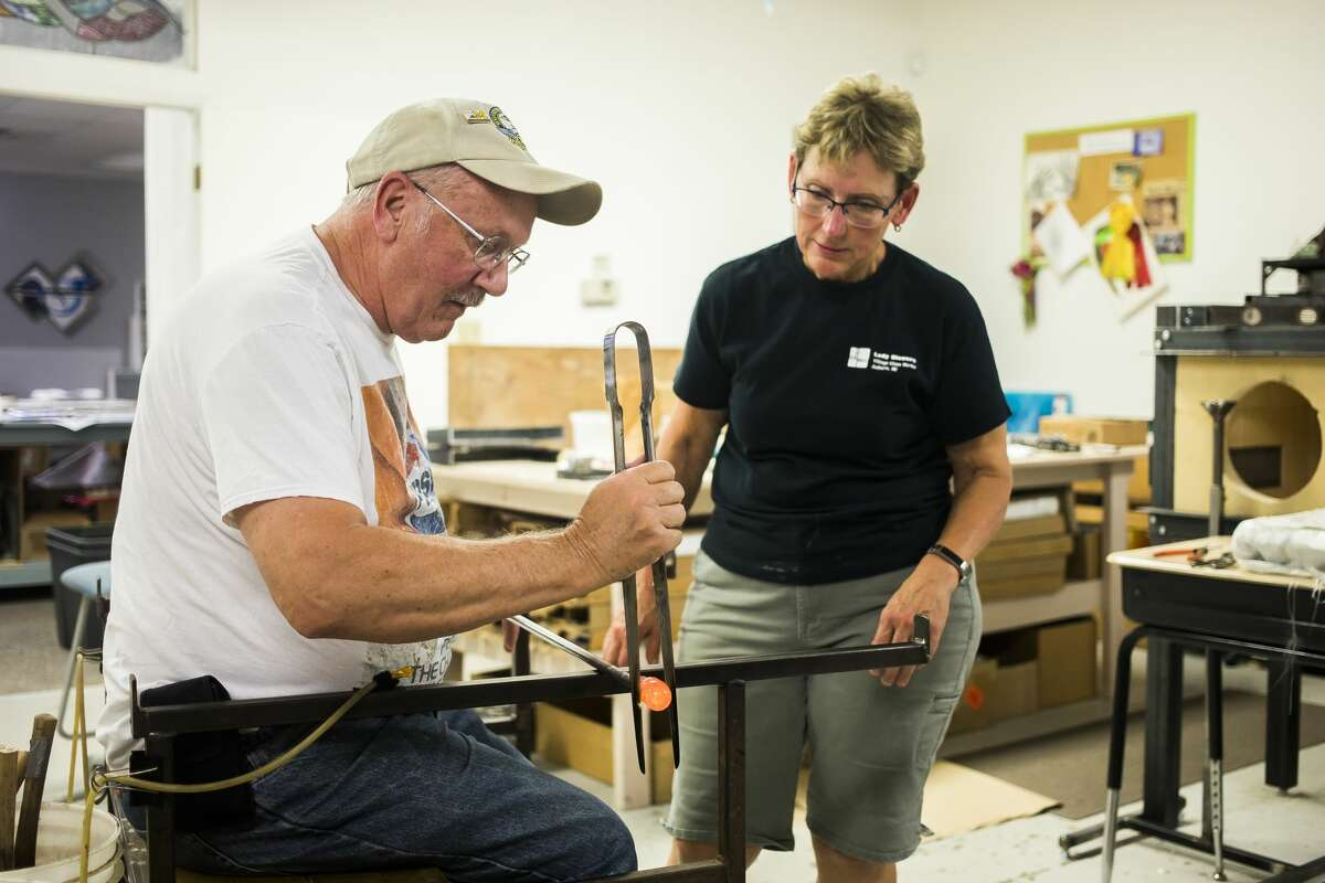 Glass blowing instructor Debra VanTol, right, assists Tom Manial of Frankenmuth, left, in shaping molten glass during the second session of a four-week glass blowing class Wednesday, Oct. 2, 2019 at Village Glass Works in Auburn. (Katy Kildee/kkildee@mdn.net)