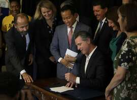 California Gov. Gavin Newsom signs bill AB 1482, Tuesday, Oct. 8, 2019, in Oakland, Calif. AB 1482 will cap rent increases at 5% each year plus inflation. The bill will also ban landlords from evicting tenants without just cause. (AP Photo/Ben Margot)