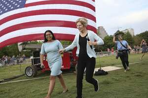 Presidential candidate Elizabeth Warren runs onto the stage with Jessica Cisneros as she holds a town hall meeting at Vic Mathias Shores at Lady Bird Lake Metro Park on September 10, 2019.