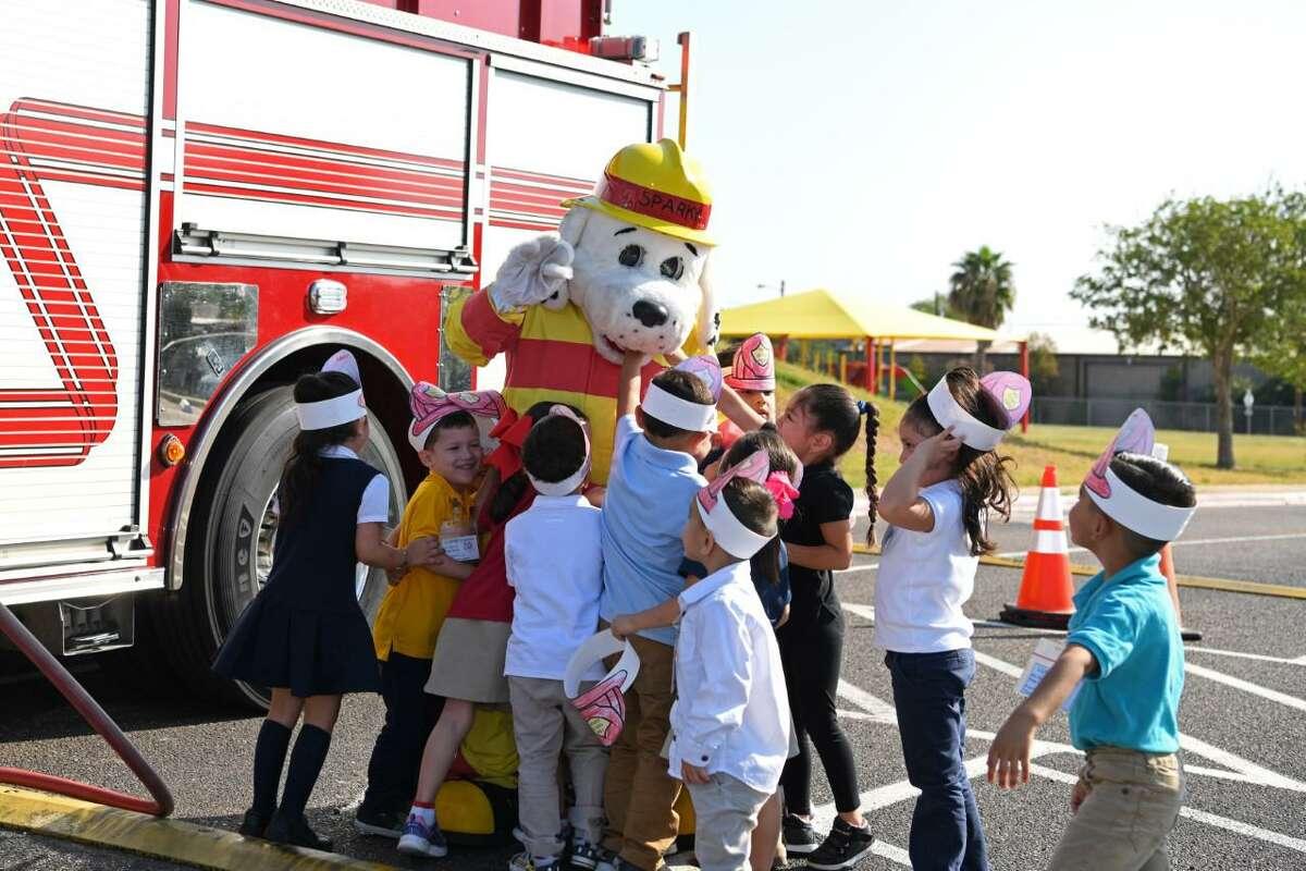Estudiantes de la escuela primaria Clarence L. Milton Elemenary School abrazan a la mascota del Departamento de Bomberos de Laredo, Sparky, durante una visita a la institución educativa para promover la prevención de incendios, el martes.