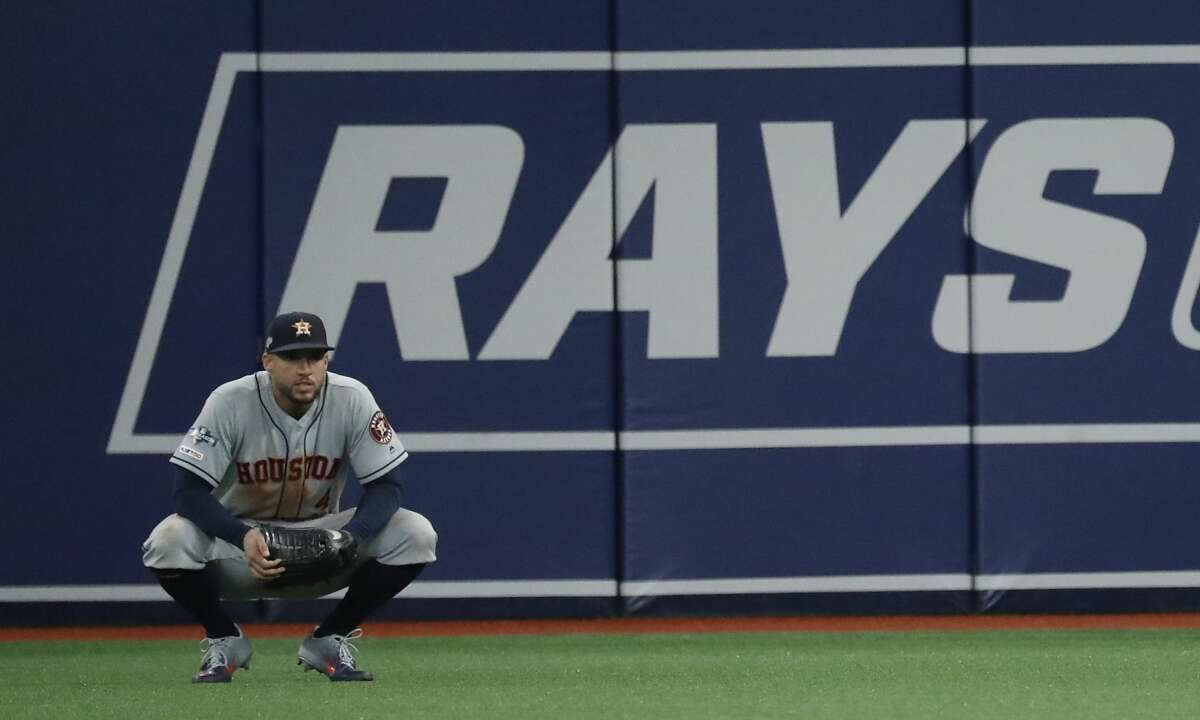 Houston Astros center fielder George Springer squats down in the outfield during a break in the action in Game 4 of the American League Division Series against the Tampa Bay Rays at Tropicana Field on Tuesday, Oct. 8, 2019, in St. Petersburg, Fla.