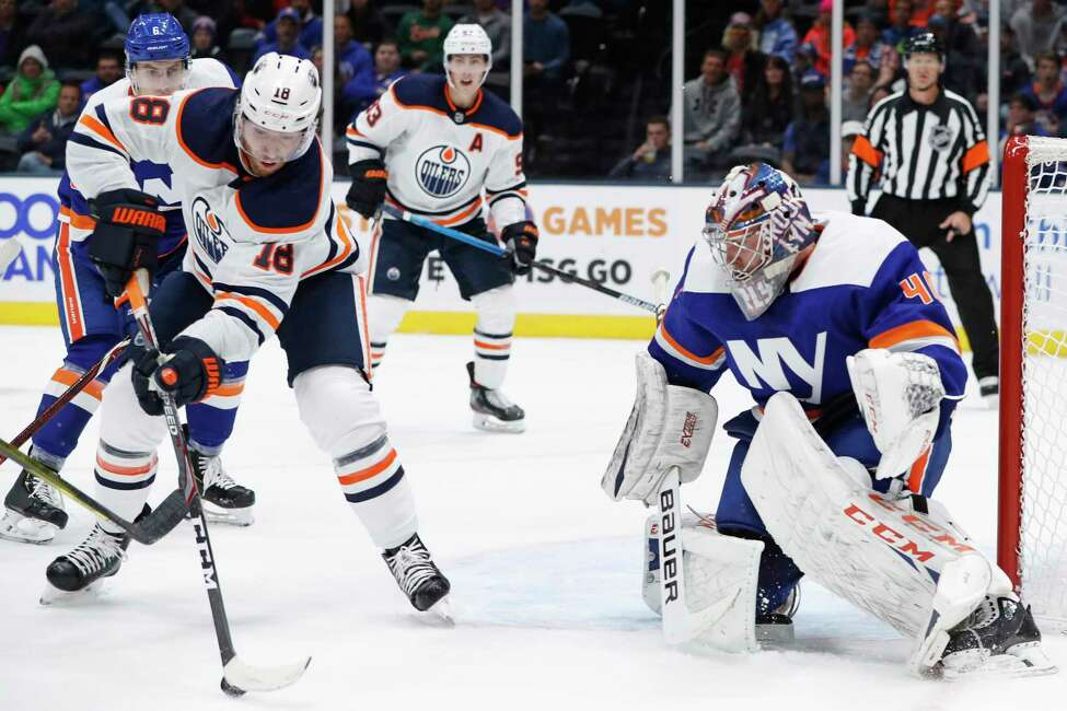 Edmonton Oilers left wing James Neal (18) sets up for a shot in front of New York Islanders goaltender Semyon Varlamov (40) as Oilers center Ryan Nugent-Hopkins (93) watches during the first period of an NHL hockey game Tuesday, Oct. 8, 2019, in Uniondale, N.Y. Neal scored four goals in the Oilers' 5-2 win. (AP Photo/Kathy Willens)