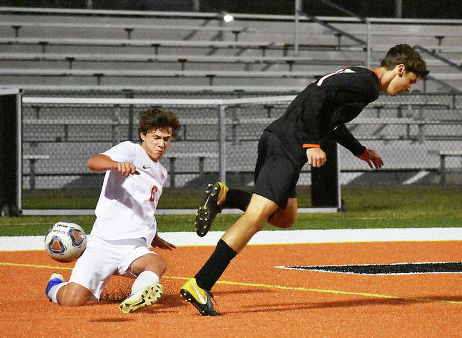 Alton defender Lucas Kercher makes a slide tackle against Edwardsville's Brennan Weller in the first half Tuesday in Southwestern Conference action in Edwardsville.