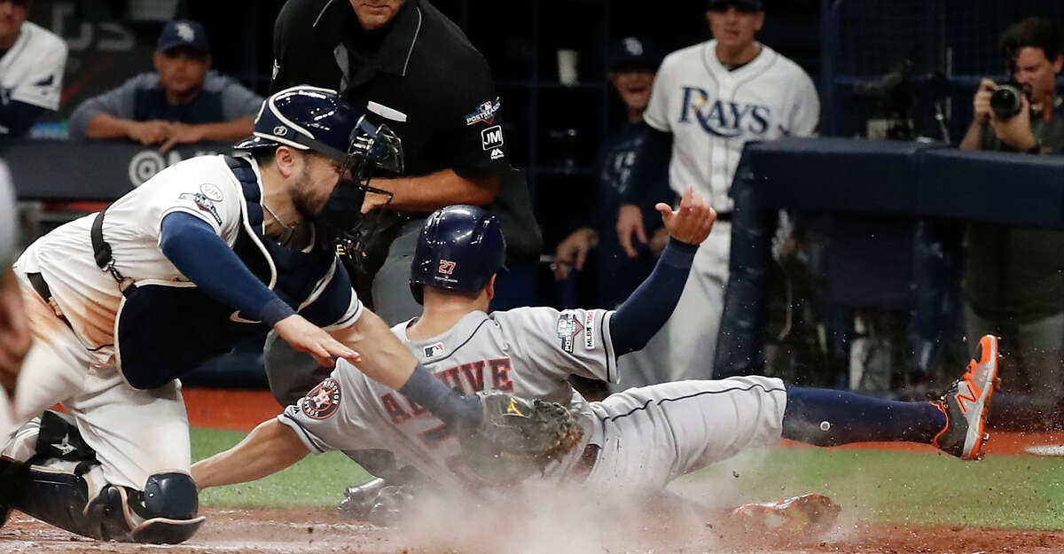 Tampa Bay Rays catcher Travis d'Arnaud tags Houston Astros second baseman Jose Altuve (27) out at home as he tries to score from first on a double by Yordan Alvarez during the fourth inning of Game 4 of the American League Division Series at Tropicana Field on Tuesday, Oct. 8, 2019, in St. Petersburg, Fla.