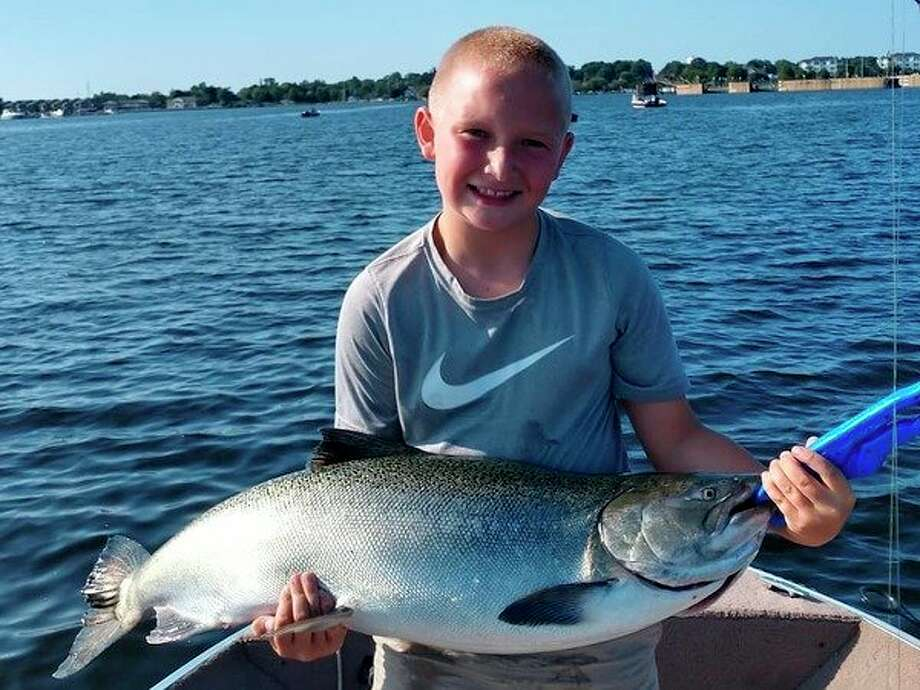 Cooper Higgins, son of Evart's Paul Higgins, shows a king salmon caught during the summer. (Courtesy photo)
