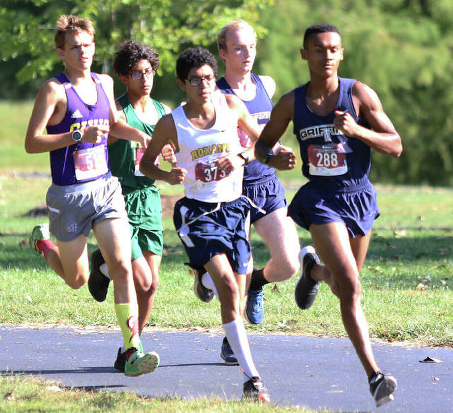From right, Father McGivney's Tyler Guthrie and Zach Brasel, Roxana's Carlos Ruvalcaba, Metro-East Lutheran's Elijah Schlessinger and Civic Memorial's Mark Eldridge run on the lead in the opening mile of the Madison County Meet;s small-schools boys race on Monday at Belk Park in Wood River. All but Schlessinger, who fell off the pace early in the second mile, missed a turn near the end of the first loop of the three-mile course and were disqualified. With the five early leaders disqualified, Schlessinger won the race. Photo: Greg Shashack / The Telegraph