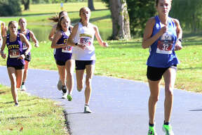 Marquette Catholic's Riley Vickrey (right) leads Roxana's Janelynn Wirth (second right) at the front of the Madison County small-schools girls cross country race Tuesday at Belk Park in Wood River.