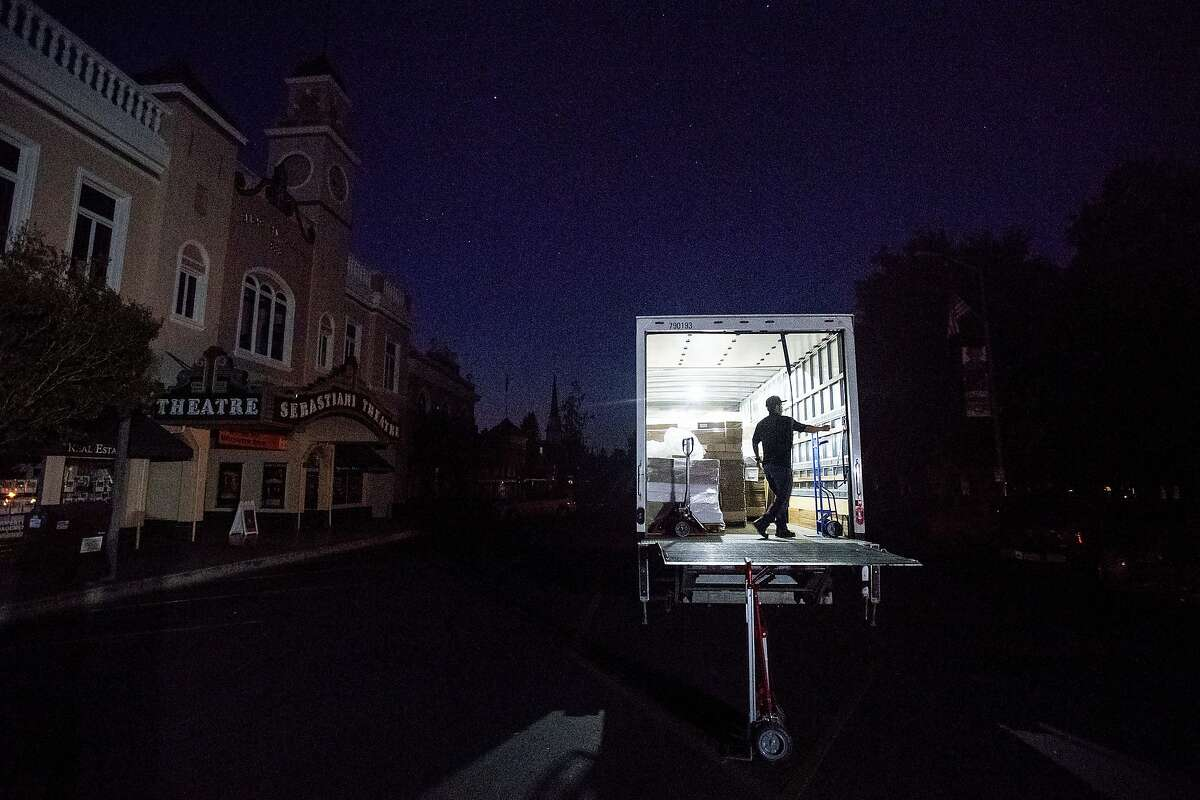Armando Espinoza delivers paper products to a cafe in downtown Sonoma, Calif., where power is turned off, on Wednesday, Oct. 9, 2019. Pacific Gas and Electric has cut power to more than half a million customers in Northern California hoping to prevent wildfires during dry, windy weather throughout the region. (AP Photo/Noah Berger)