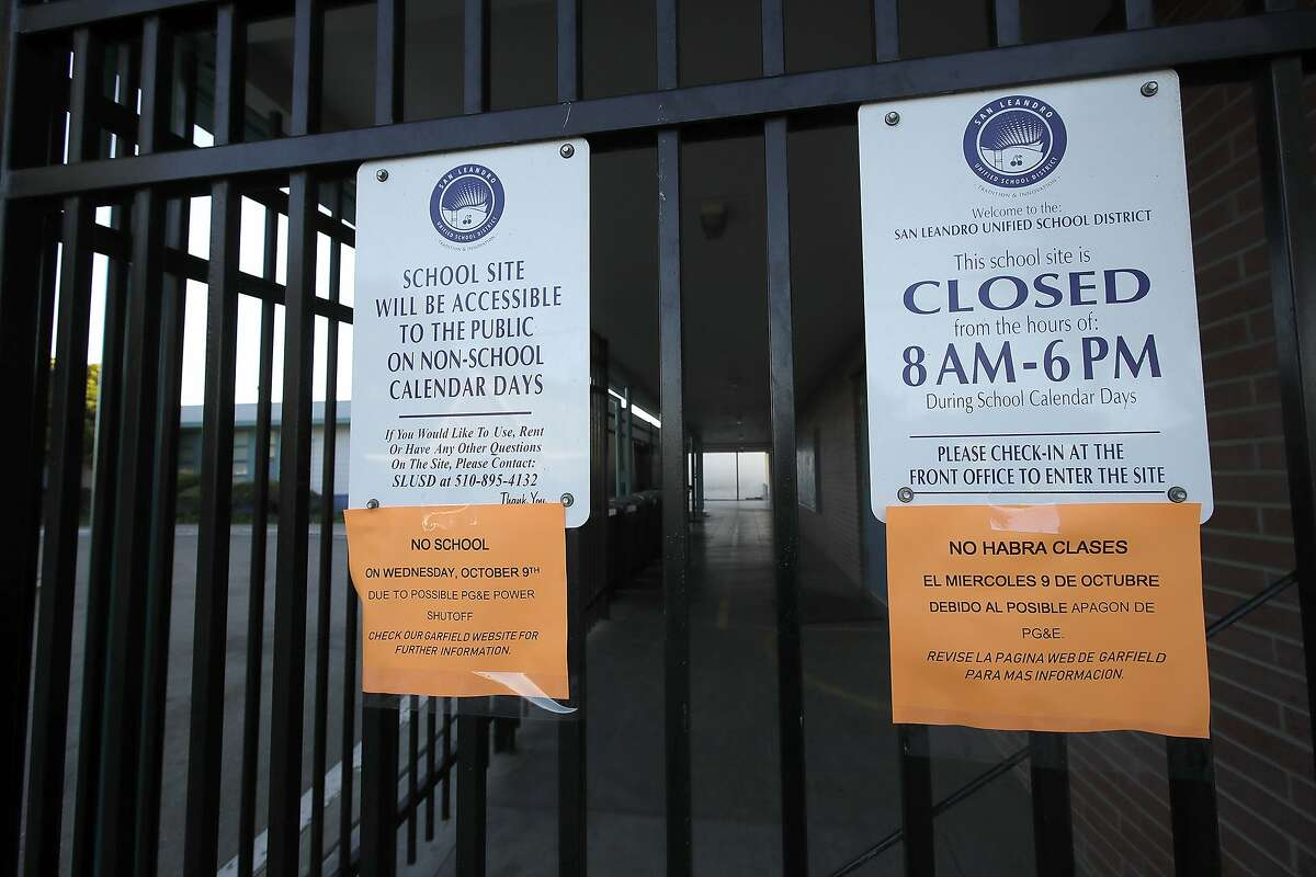 Signs are posted on the doors of Garfield Elementary School informing that the school is closed due to Pacific Gas & Electric possibly shutting off power on Wednesday, Oct. 9, 2019, in San Leandro, Calif. PG&E has cut power to more than half a million customers in Northern California hoping to prevent wildfires during dry, windy weather throughout the region. (AP Photo/Ben Margot)