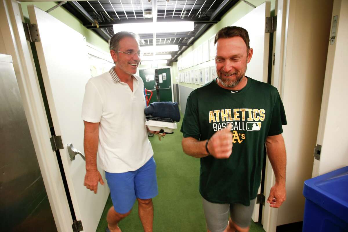 Oakland A's Executive Vice President of Baseball Operations Billy Beane and bench coach Mark Kotsay share a laugh in 2016.