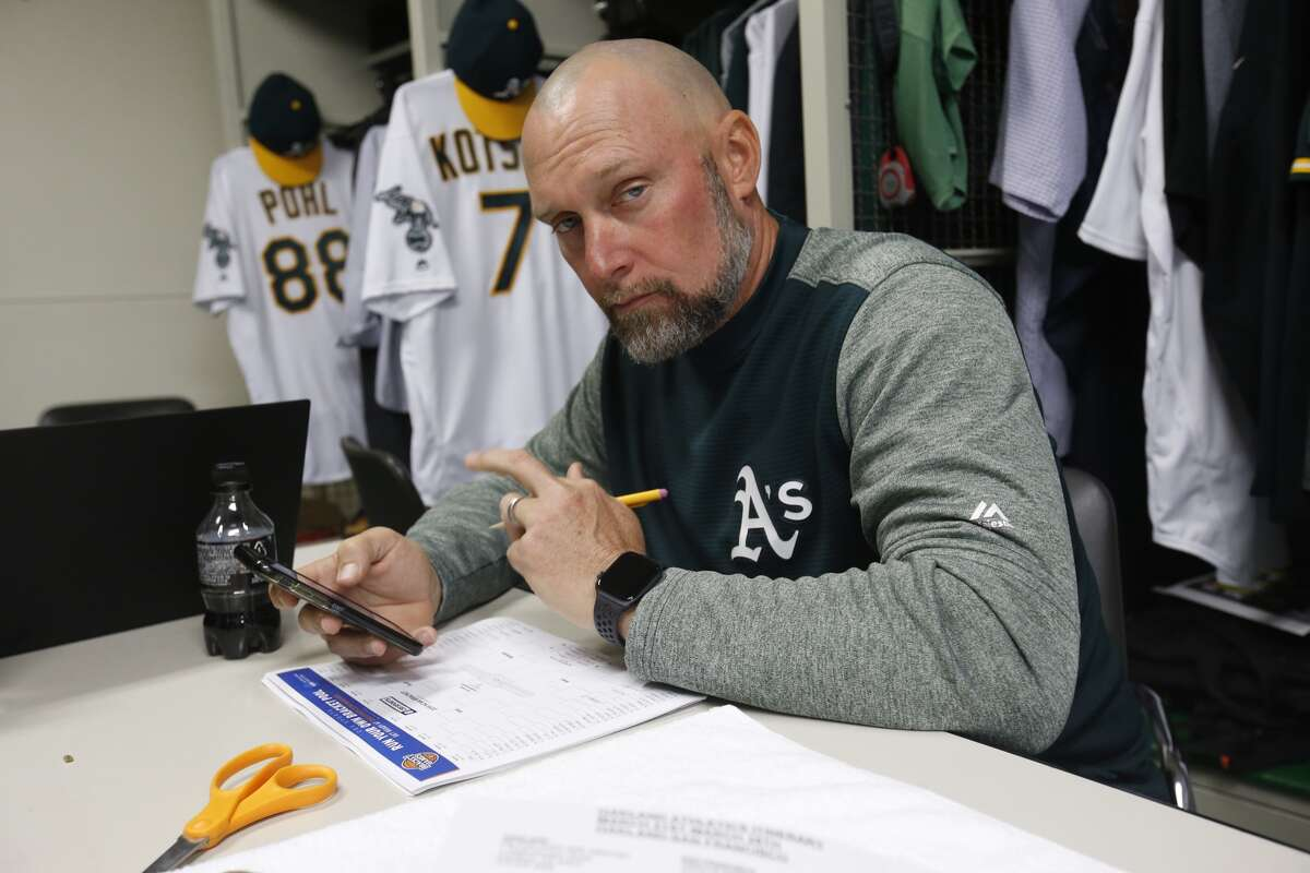 Quality Control Coach Mark Kotsay of the Oakland Athletics works on his Final Four bracket in the clubhouse prior to the game against the Seattle Mariners at the Tokyo Dome in March. Kotsay reportedly is a candidate for manager of the San Francisco Giants.