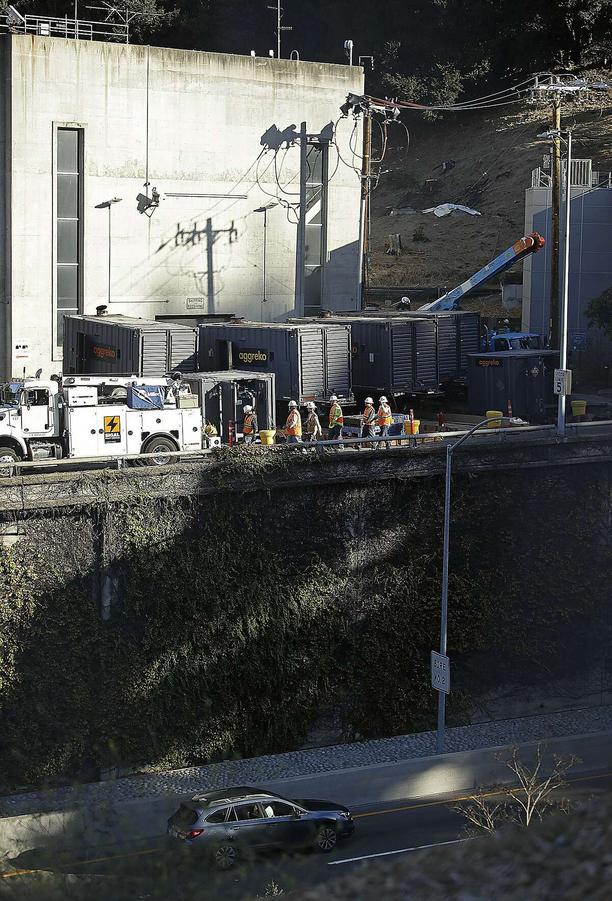 Crews work to connect generators at the Caldecott Tunnel on Wednesday, Oct. 9, 2019, in Oakland, Calif. Pacific Gas & Electric has cut power to more than half a million customers in Northern California hoping to prevent wildfires during dry, windy weather throughout the region. (AP Photo/Ben Margot)