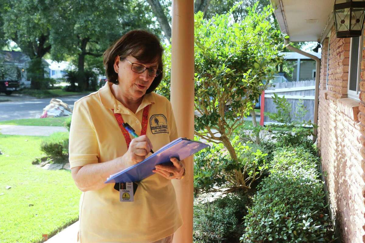 Christy Hardin, from Anniston, Alabama, makes notes on the water level from TS Imelda flooding as she approaches a home in the city of Liberty. Hardin was working as an assessor for the Southern Baptist Disaster Relief organization.