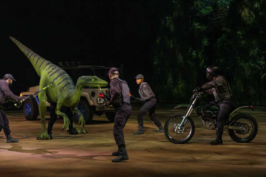 Jeanie, a Troodon, encounters InGen security forces in Gyrosphere Valley in Jurassic World Live Tour (Feld Entertainment)