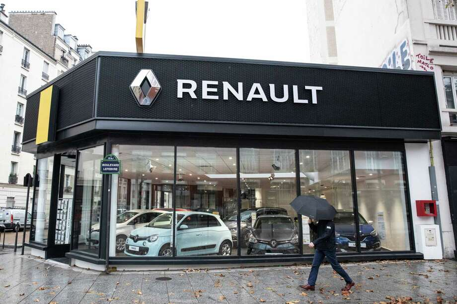 A pedestrian shelters under an umbrella outside a Renault showroom in Paris on Nov. 20, 2018. Photo: Bloomberg Photo By Christophe Morin. / © 2018 Bloomberg Finance LP