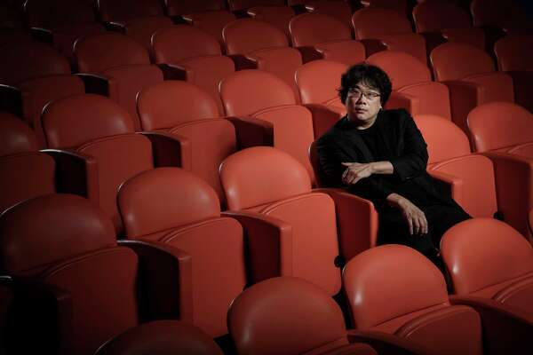 """This Oct. 8, 2019 photo shows filmmaker Bong Joon-Ho posing for a portrait at the Whitby Hotel screening room in New York to promote his film """"Parasite."""" The film will open in theaters Friday having already amassed $70.9 million in Bong's native South Korea. In May, """"Parasite"""" won the Palme d'Or at the Cannes Film Festival, a first for a Korean film. (Photo by Christopher Smith/Invision/AP)"""