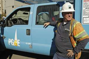 A Pacific Gas & Electric stands beside his truck near the Caldecott Tunnel Wednesday, Oct. 9, 2019, in Oakland, Calif. Pacific Gas & Electric has cut power to more than half a million customers in Northern California hoping to prevent wildfires during dry, windy weather throughout the region. Emergency generators were set up by CalTrans to keep the Caldecott Tunnel open during a possible power outage. (AP Photo/Ben Margot)