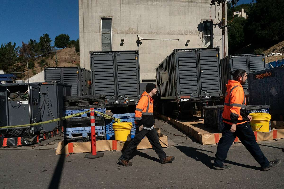Caltrans Zachary Laird and a co-worker walk past leased generators that are powering the Caldecott Tunnels on Wednesday, Oct. 9, 2019, in Oakland, Calif.