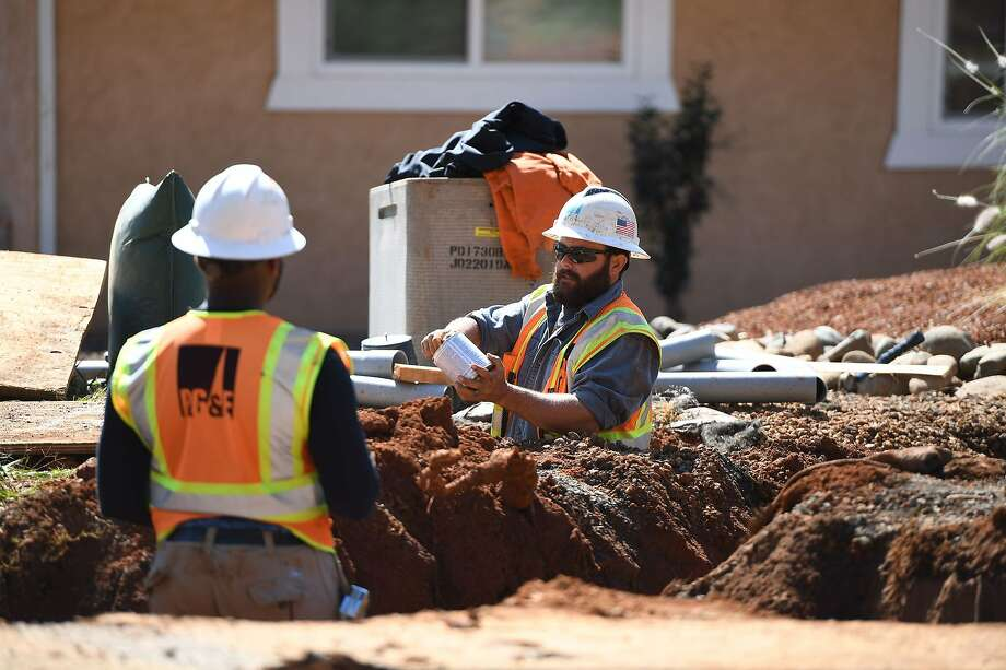 Pacific Gas & Electric Co. (PG&E) workers install conduit in trenches for underground electric lines in Paradise, California, October 1, 2019. - Rolling blackouts set to affect millions of Californians began  as a utility company started switching off power to an unprecedented number of households in the face of windy weather that raises the risk of wildfires. Pacific Gas & Electric, which announced the deliberate outage, is working to prevent a repeat of a catastrophe last November in which faulty power lines it owned were determined to have sparked California's deadliest wildfire in modern history. Photo: Robyn Beck, AFP Via Getty Images
