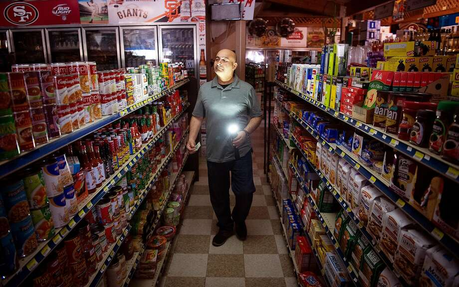 Bait Shop Market owner Akber Jiwani surveys his store with a flashlight during a state-wide blackout done as a preventative measure to combat wildfires in Sausalito on Wednesday, Oct. 09, 2019. Jiwani says he expects to lose nearly $5,000 worth of products like ice cream and other perishables during the black out. Photo: Josh Edelson / Josh Edelson / Special To The Chronicle