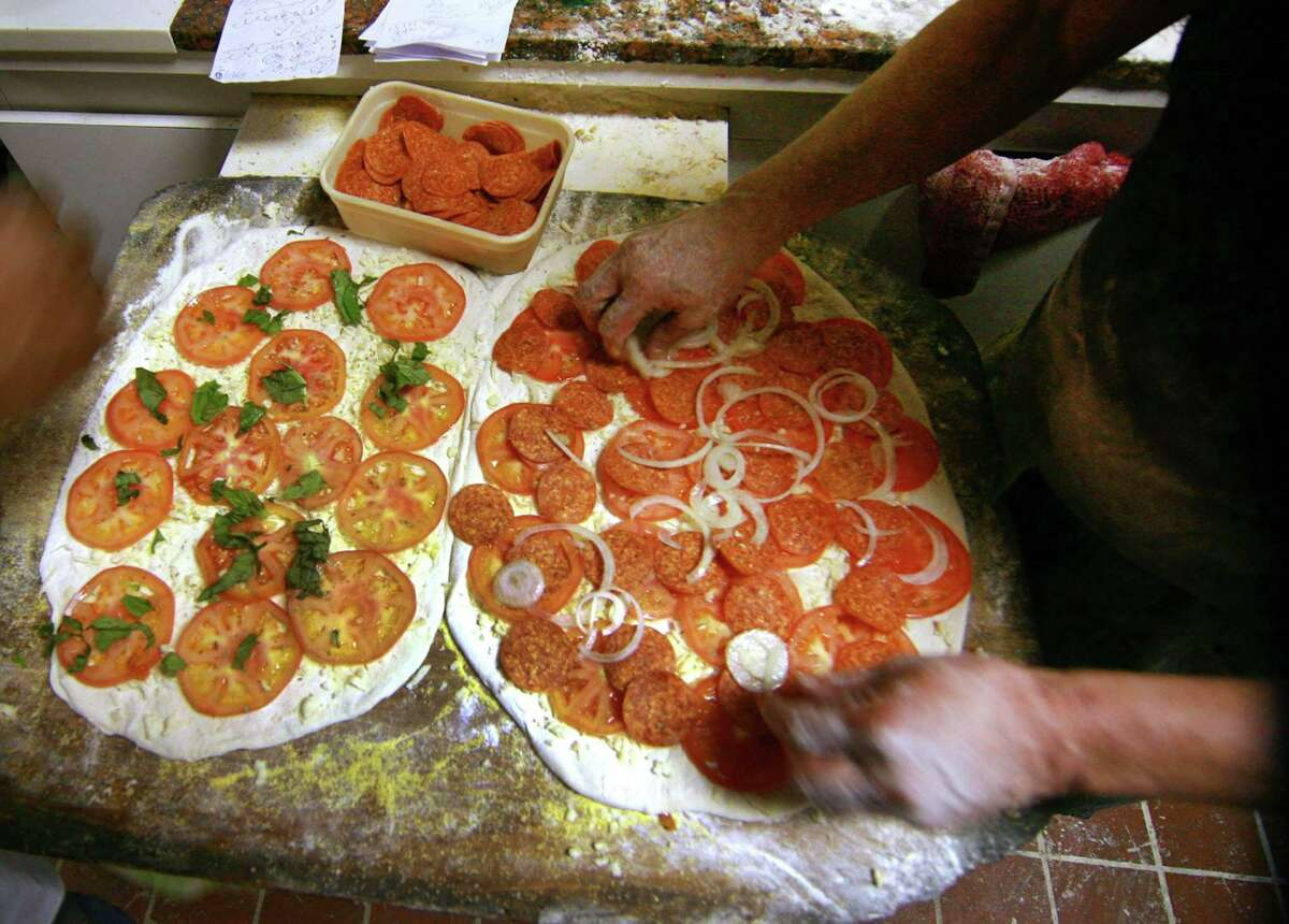 Workers put toppings on an order at Sally's Apizza on Wooster Street in New Haven. Lineage Hospitality, an investment consortium that owns Sally's, plans to open replicas of the iconic pizzeria across the country, starting at the new Norwalk mall.