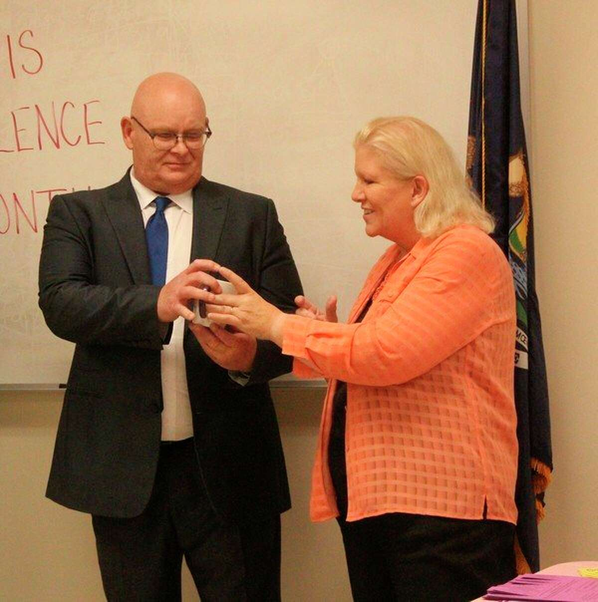 Teresa Mora (right),WISE Osceola County domestic violence outreach coordinator, presentedOsceola County Assistant Prosecutor Cameron Harwell with a mug to thank him for his work with survivors of domestic violence in the area.(Pioneer photo/Taylor Fussman)