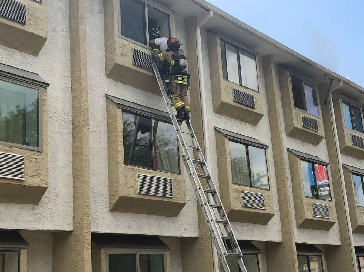 People are evacuating a Motel 6 in Spring as firefighters battle a three-alarm fire.