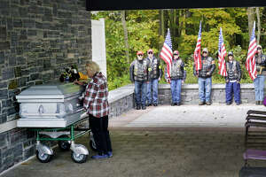 Joyce Rescigno of Stillwater places her hand on the casket of veteran Ambrose Jacob during his funeral service at the Gerald B.H. Solomon Saratoga National Cemetery on Wednesday, October 9, 2019, in Schuylerville, N.Y. Rescigno said that her brother and five friends are also buried at the cemetery.  (Paul Buckowski/Times Union)
