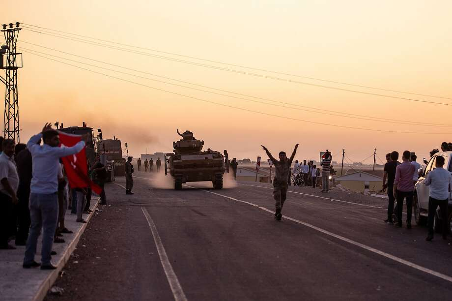 People wave as Turkish soldiers prepare to cross the border into Syria on October 09, 2019 in Akcakale, Turkey. The military action is part of a campaign to extend Turkish control of more of northern Syria, a large swath of which is currently held by Syrian Kurds, whom Turkey regards as a threat. U.S. President Donald Trump granted tacit American approval to this campaign, withdrawing his country's troops from several Syrian outposts near the Turkish border.  Photo: Burak Kara, Getty Images