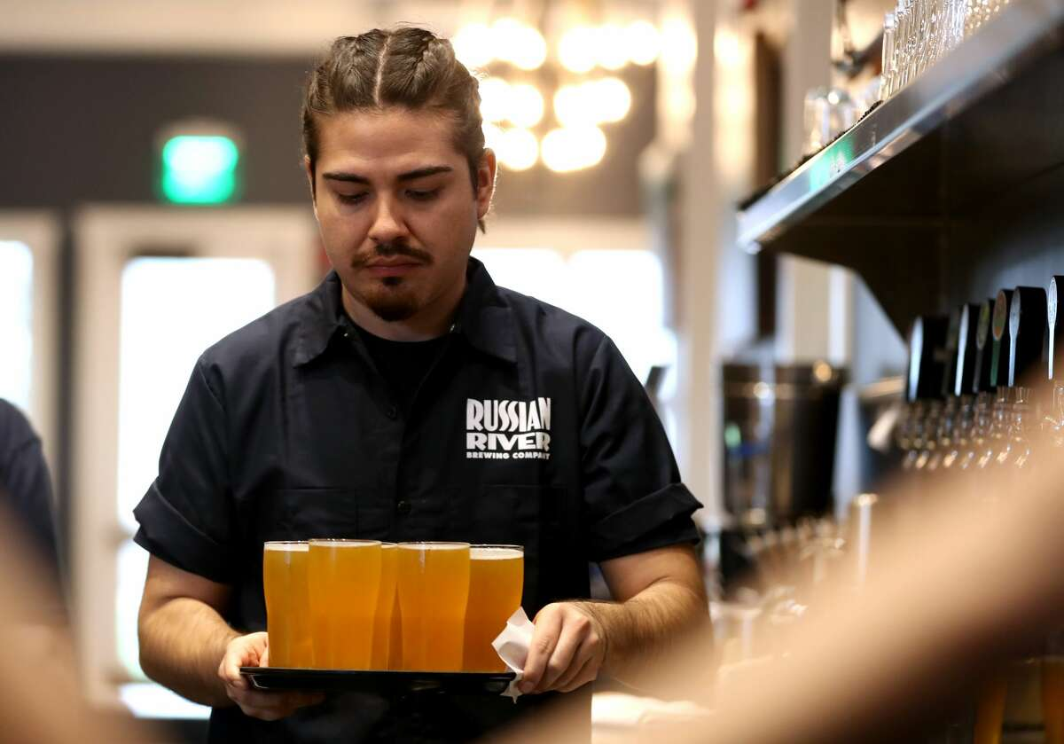 FILE - Alan Rodriguez carries a tray of Russian River Brewing's Pliny the Younger at the Russian River Brewing Company on February 01, 2019 in Windsor, California. Russian River had to turn to renting a massive generator in order to keep the brewery going during the massive PG&E power shutoff.