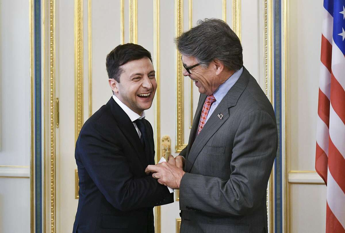 Ukrainian new President Volodymyr Zelenskiy, left, and US Energy Secretary Rick Perry share a joke during their meeting in Kiev, Ukraine, Monday, May 20, 2019. Television star Volodymyr Zelenskiy has been sworn in as Ukraine's next president after he beat the incumbent at the polls last month. (Mykola Lazarenko/Presidential Press Service Pool Photo via AP)
