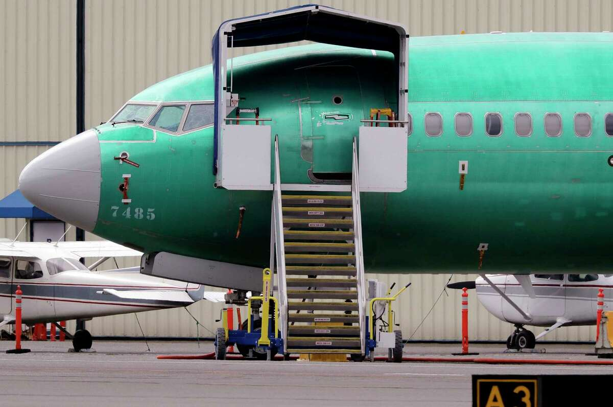 FILE - In this April 8, 2019, file photo a Boeing 737 MAX 7 jet is parked near single engine planes at the airport adjacent to a Boeing Co. production facility in Renton, Wash. Boeing said Tuesday, Oct. 8, that it delivered just 26 planes in September, down from 87 a year earlier, when it was ramping up Max production. (AP Photo/Elaine Thompson, File)