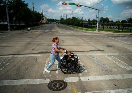 Gina Rios crosses Fulton Street at Quitman street with her grandson Mason, 1, where the paint marking the crosswalk is worn away in the Near Northside neighborhood of Houston on Oct. 9.