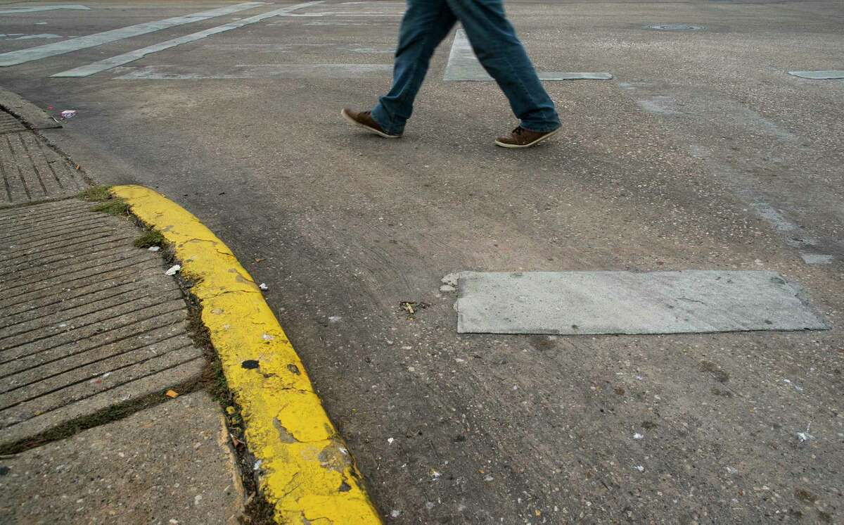 The paint marking the crosswalk is worn away at the intersection of Quitman and Fulton Streets in the Near Northside neighborhood of Houston as a pedestrian crosses on Oct. 9.