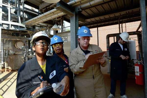 From left, Brandy Bean-Plair, Keyola Arvie, and Maranda Curry confer as they check levels and take readings during their shift in Thomas Day's petrochemical operations working classroom at LIT. The small plant mixes and separates water and propylene glycol, providing hands-on education for students nearing graduation and moving on to find work in the petrochemical industry. Photo taken Friday, October 04, 2019 Kim Brent/The Enterprise
