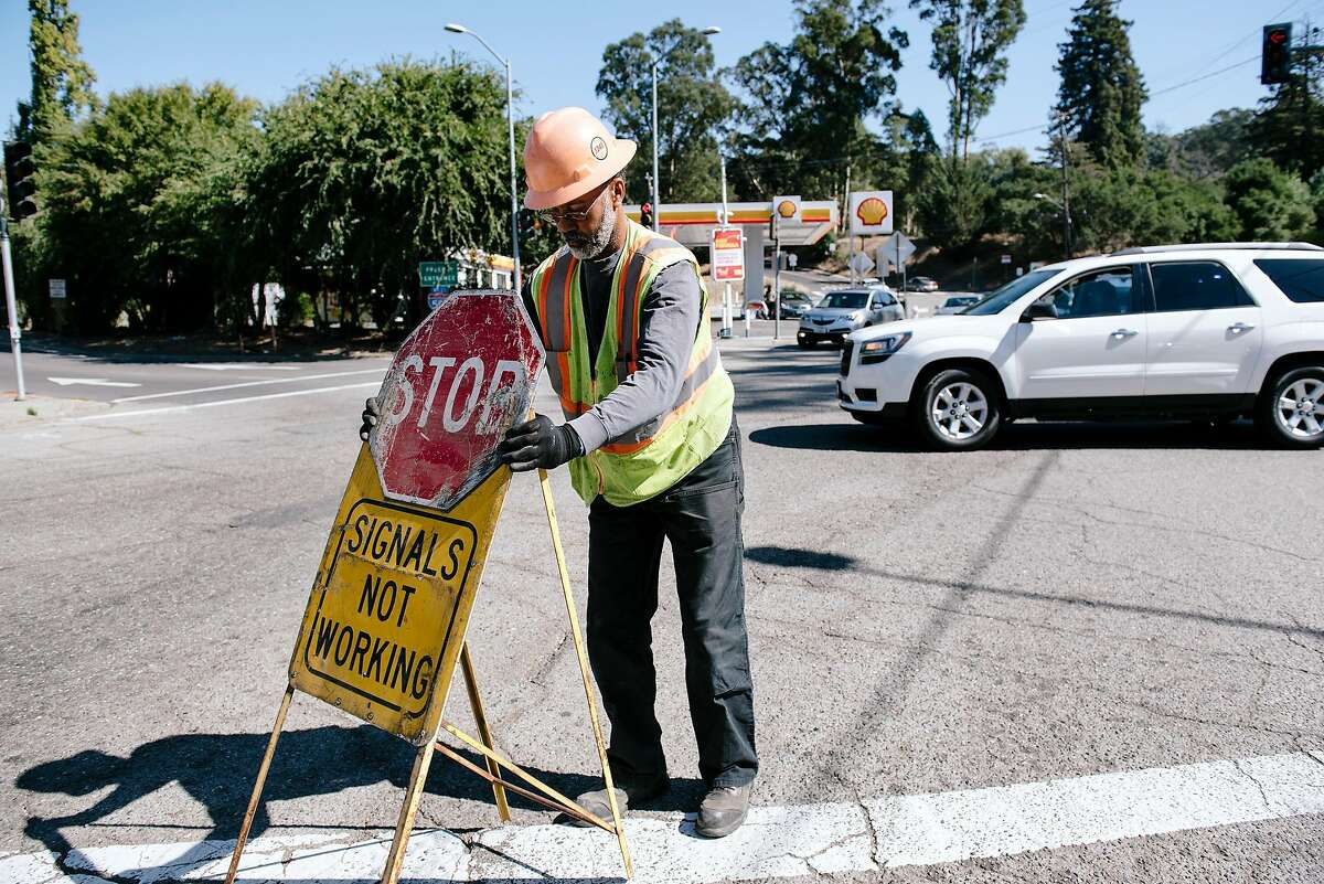 Tyrone Rowe with the Oakland Department of Transportation sets out stop signs at the corned fo Golf Links Road and 98th Avenue after preemptively setting the traffic lights to flashing red in lieu of scheduled power outages in Oakland, California, on Friday, Oct. 9, 2019.