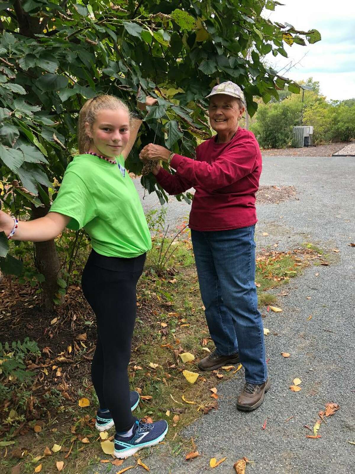 A Rensselaer City School District student and a HVCC Center for Creative Retirement participant choose just the right spot to place a pine cone bird feeder they made together at the BASF Nature Center during its 2nd Annual Inter-generational Nature Day. (Fran Pilato)