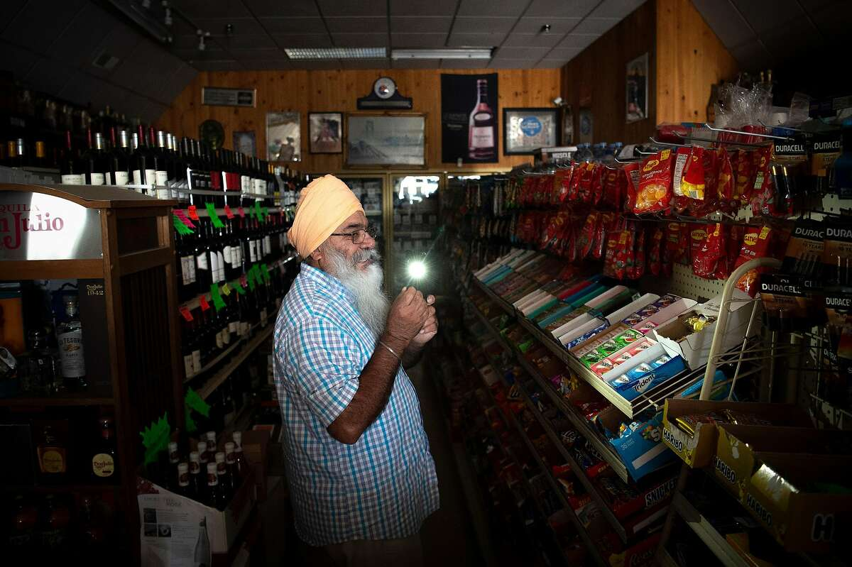 Pal's Liquor Wine & Grocery store owner Harjinder Saehwal walks around his store using his phone's flashlight during a statewide blackout done as a preventative measure to combat wildfires in Sausalito on Wednesday, Oct. 09, 2019.