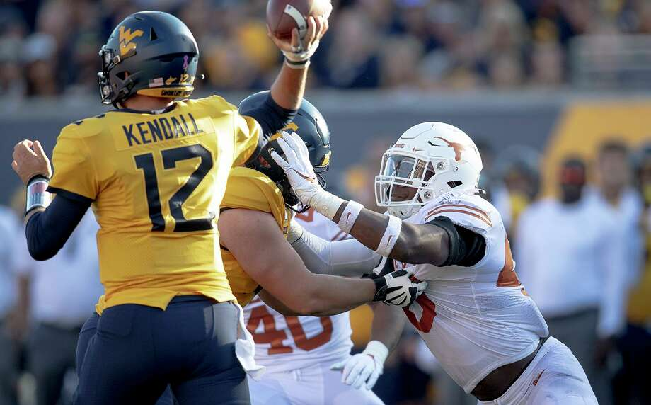 Texas linebacker Joseph Ossai (46) pressures West Virginia quarterback Austin Kendall (12) during an NCAA college football game on Saturday, Oct. 5, 2019, in Morgantown, W.Va. Photo: Nick Wagner, MBO / Associated Press / Austin American-Statesman