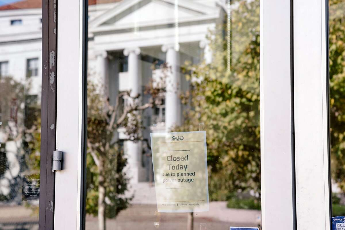 Sproul Hall is seen reflected in a window of the Golden Bear restaurant where a sign announces its closure at UC Berkeley in Berkeley, California, on Friday, Oct. 9, 2019. UC Berkeley canceled classes and closed the school on Wednesday in the face of looming planned power shutoff's by PG&E.