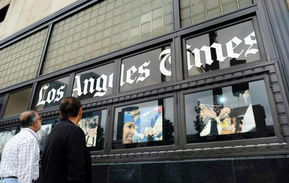 FILE - In this May 16, 2016, file photo, pedestrians look at news photos posted outside the Los Angeles Times building in downtown Los Angeles. California newspaper companies have one year to figure out how they'll comply with a pending state law that could require them to treat newspaper delivery people like employees rather than contractors. At issue is a bill, AB5, sent to Gov. Gavin Newsom that makes it harder for companies to treat their workers as contractors who are not entitled to minimum wage and certain benefits. (AP Photo/Richard Vogel, File) Photo: Richard Vogel, STF / Associated Press / Copyright 2016 The Associated Press. All rights reserved. This material may not be published, broadcast, rewritten or redistribu