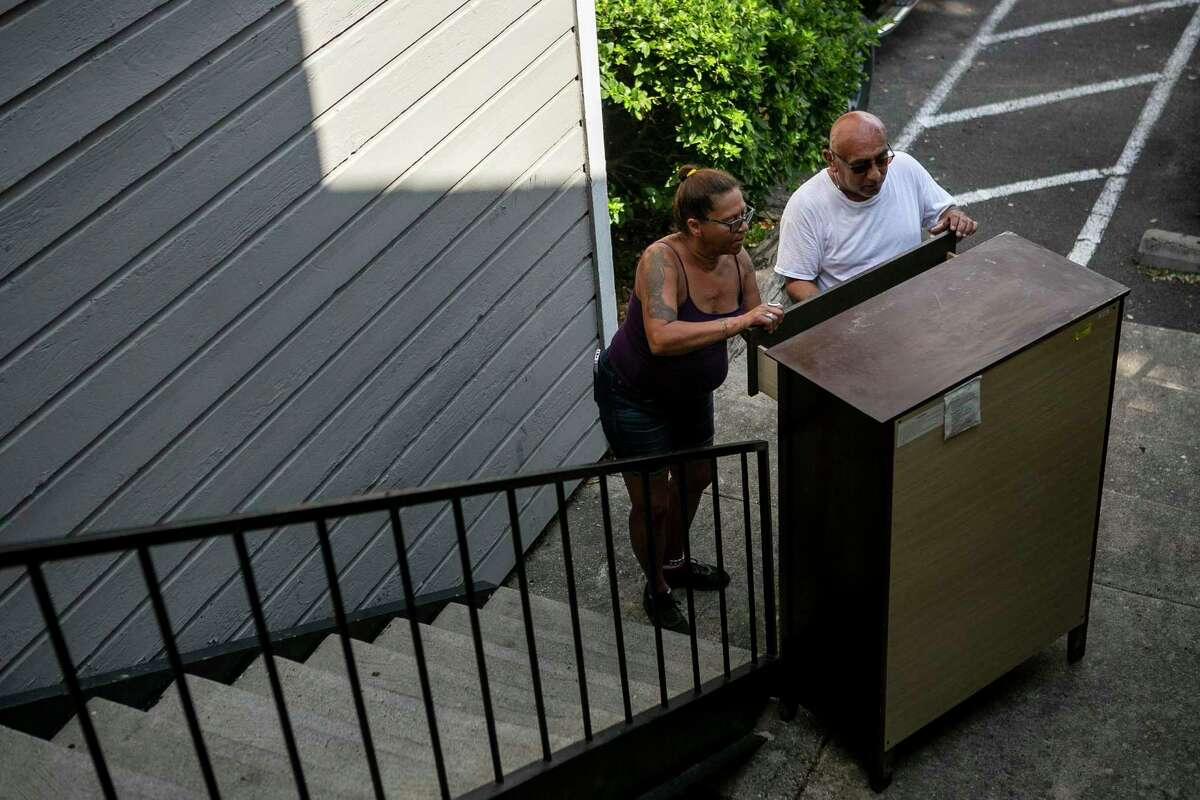 Mary Ann Stacey and Santos Galindo examine a dresser retrieved from her former apartment building before the burned structure was demolished at Villa Rodriguez Apartments on Wednesday. The crew recovered some undamaged furniture from her apartment, including the dresser and a table set that she had just purchased.