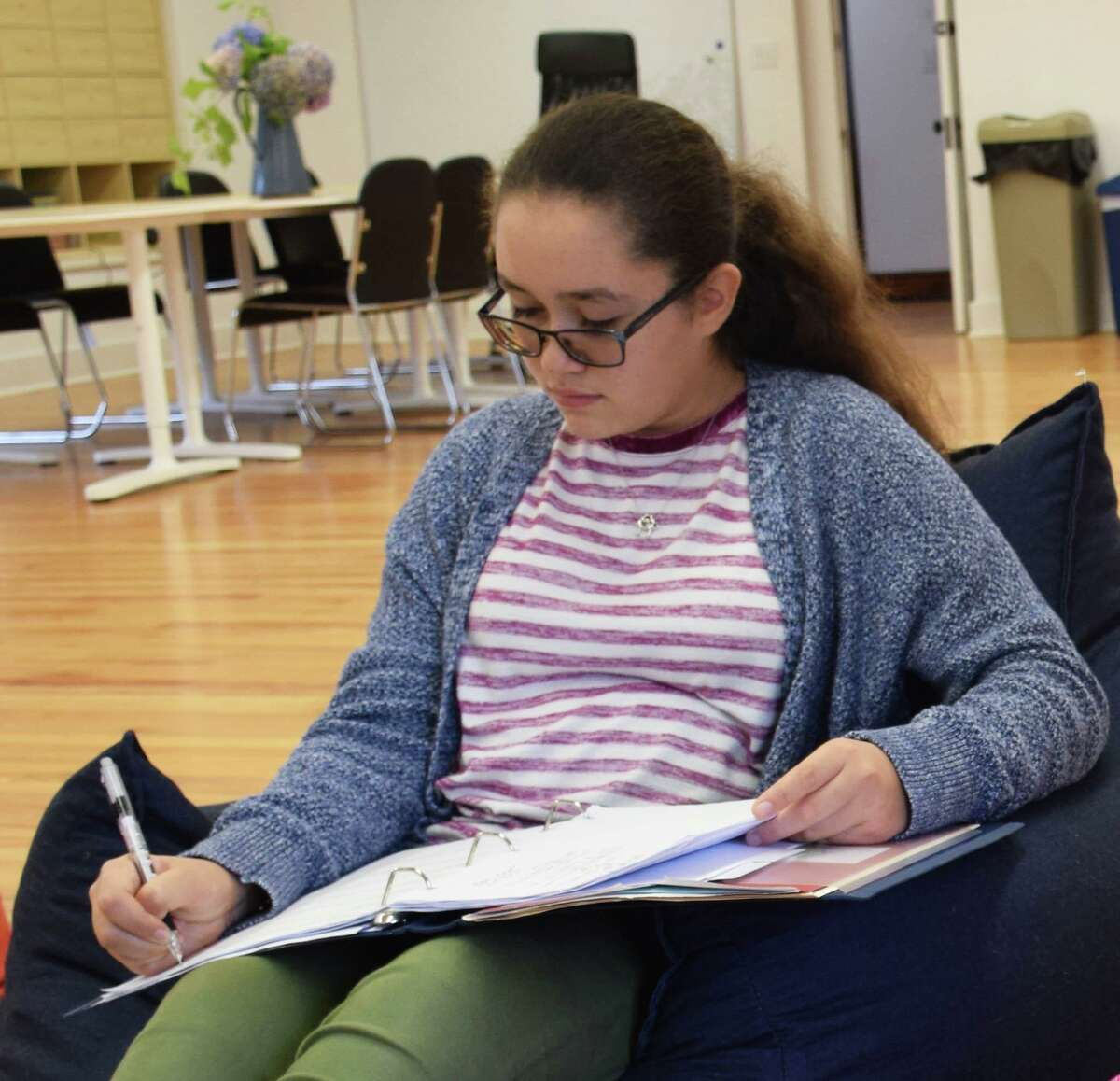 Antonia Rodriguez works on homework on the open third floor, where tables, locker cubbies and a nook for reading and homework is available.