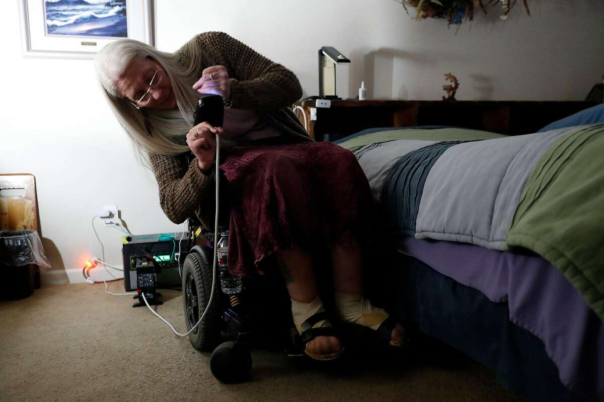 With her house being partially powered by a generator, quadriplegic Gina Biter-Mundt plugs in her electric wheelchair during PG&E power shut off at her home In Napa, Calif., on Wednesday, October 9, 2019.