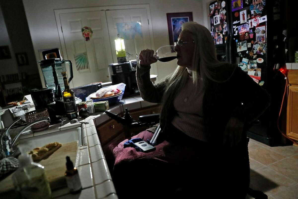 With power from a generator providing light, quadriplegic Gina Biter-Mundt enjoys a sip of wine while eating in the kitchen during PG&E power shut off at her home In Napa, Calif., on Wednesday, October 9, 2019.